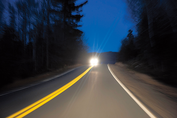 Car driving at night with high beams driving down the road.