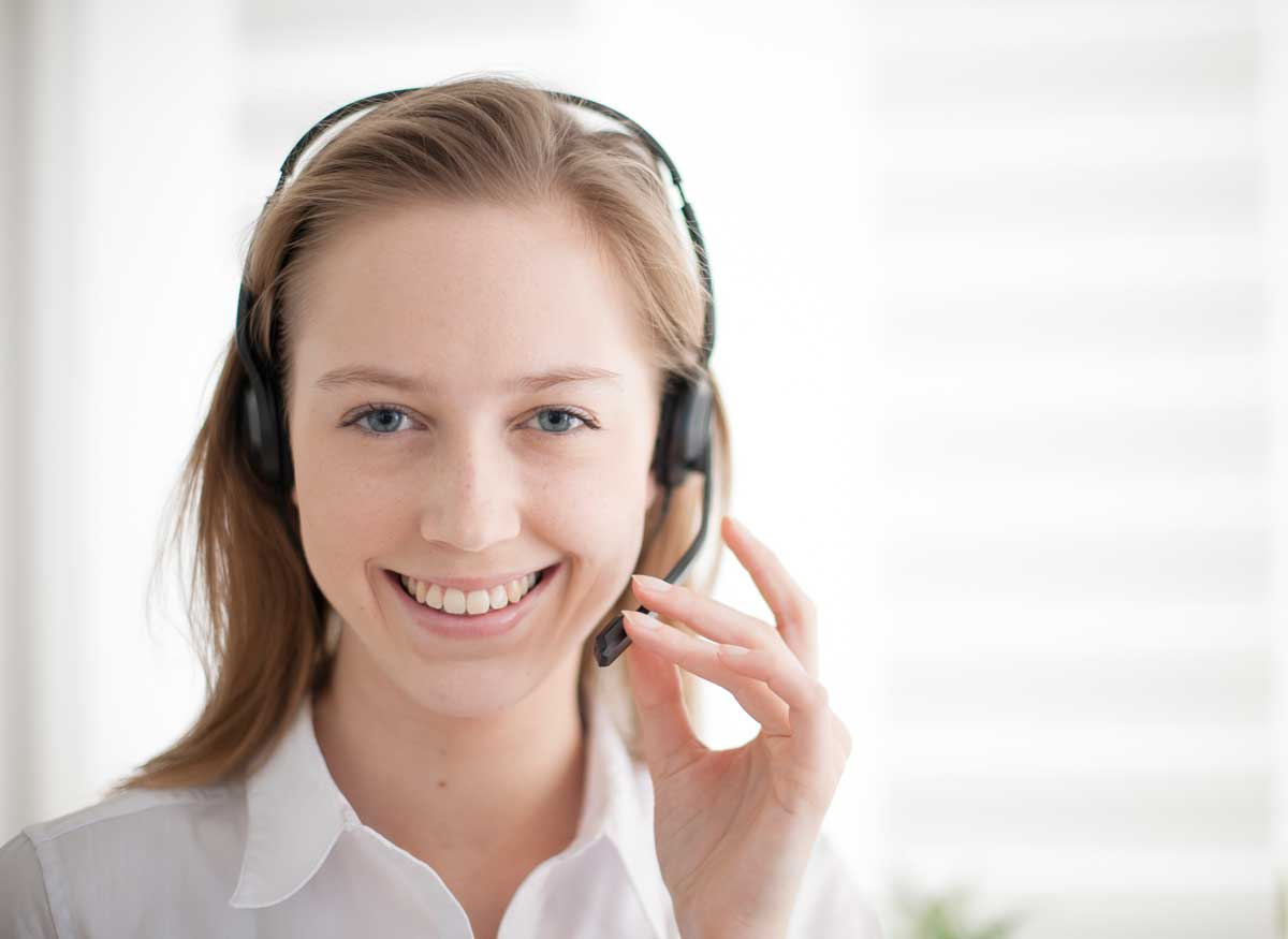Photo of a person using a headset to talk on the phone.