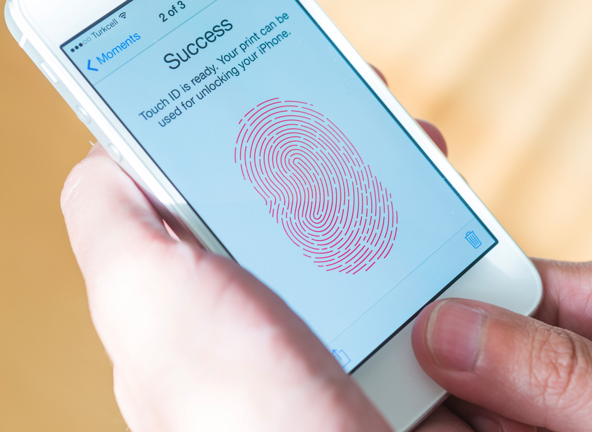Picture of someone using their thumb print to unlock their phone.