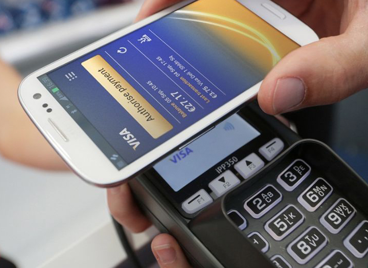Someone using NFC (Near Field Communication) to wave their smartphone at a store register to pay.