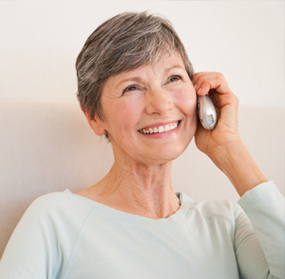 An older woman talking on the phone and smiling.