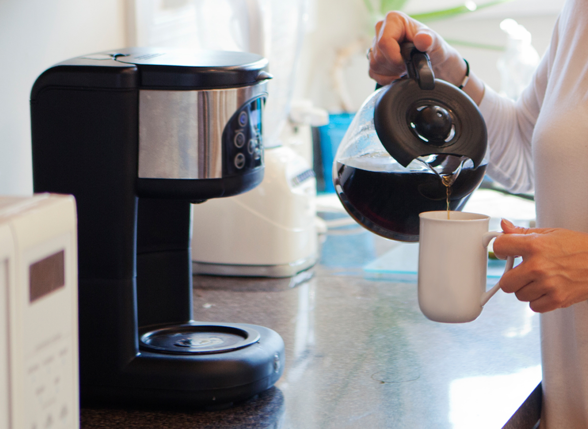 Woman pouring a cup of coffee while machine pauses brewing.