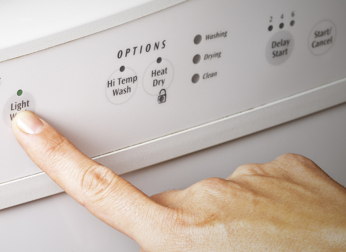 Picture of someone pushing the heated dry button on their dishwasher conotrol panel.