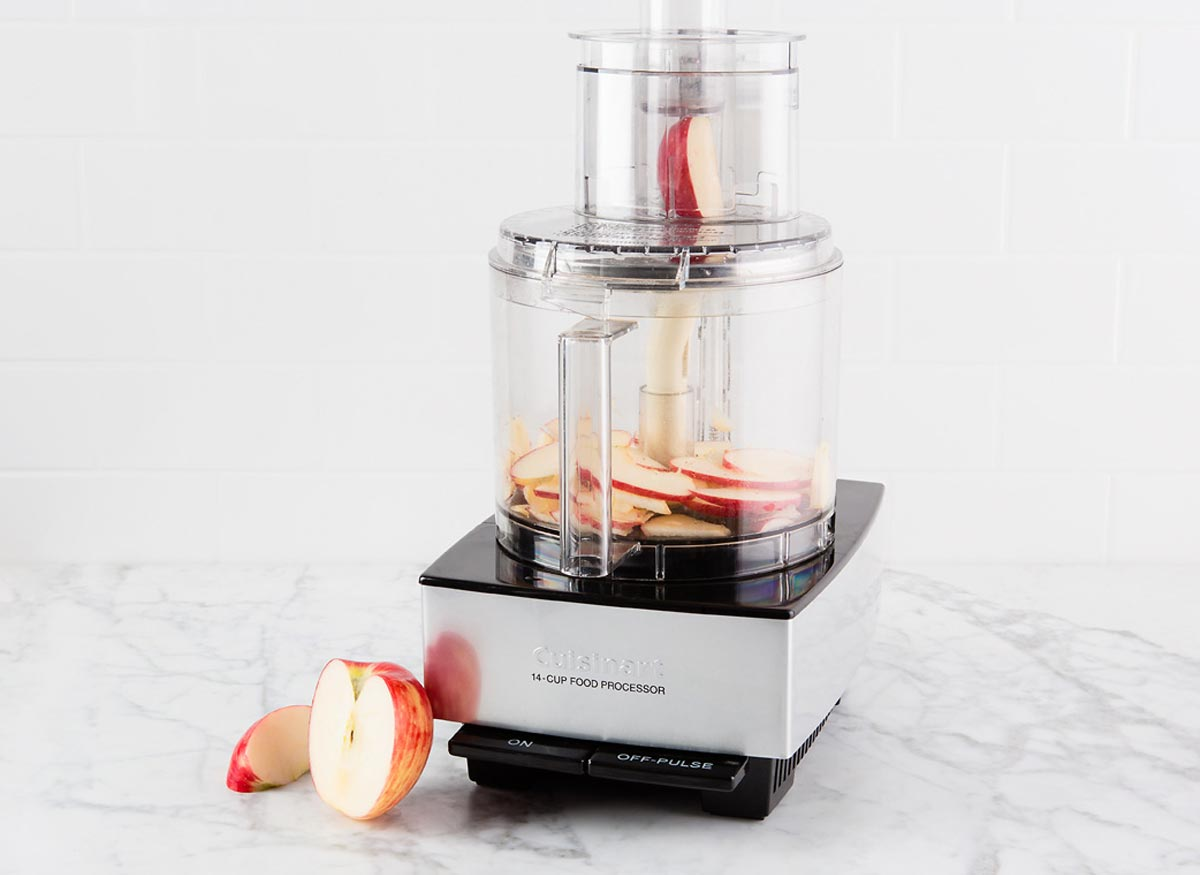 Photo of an apple slice in the feed tube of a food processor.