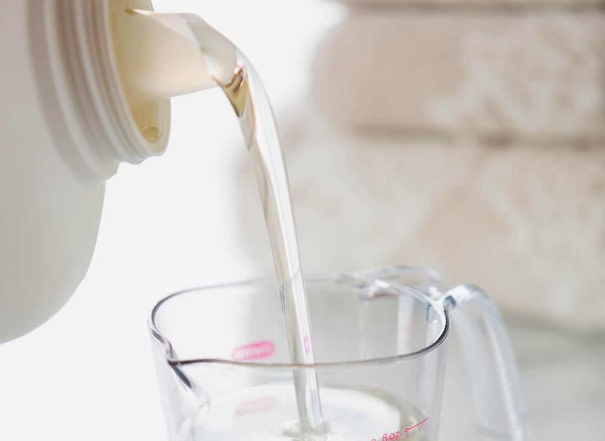 Photo of a clear laundry detergent being poured into a measuring cup.