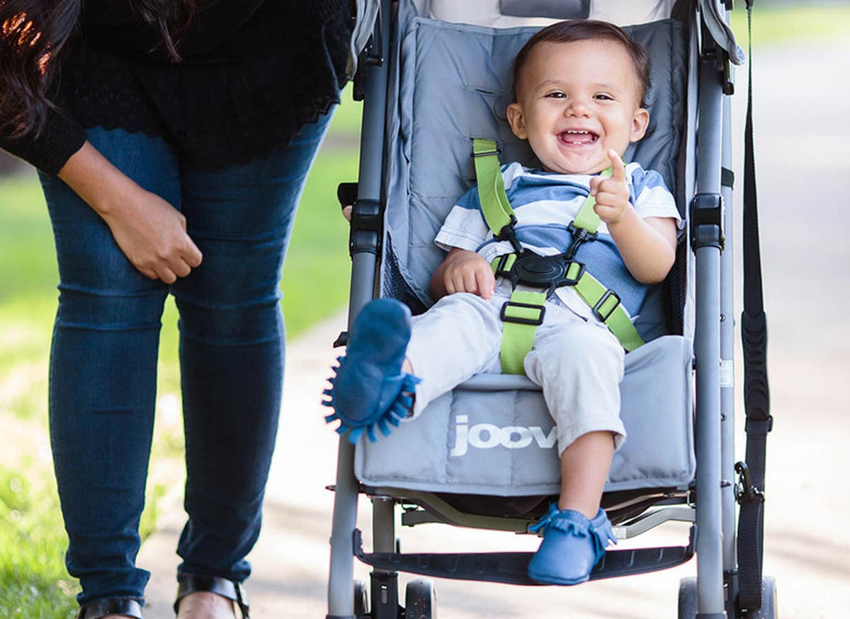 Photo of a child sitting in a stroller that has a five-point restraint system.
