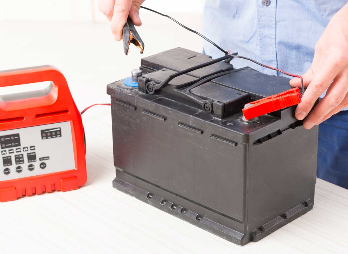 Person attaching a float charger to a car battery.
