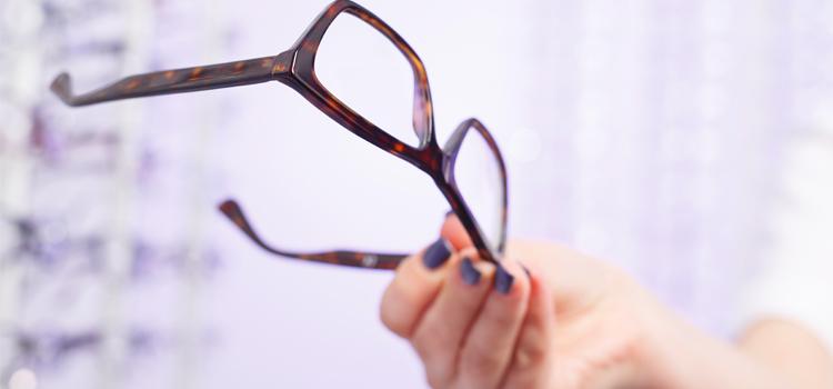 Hand holding pair of eyeglass lenses.