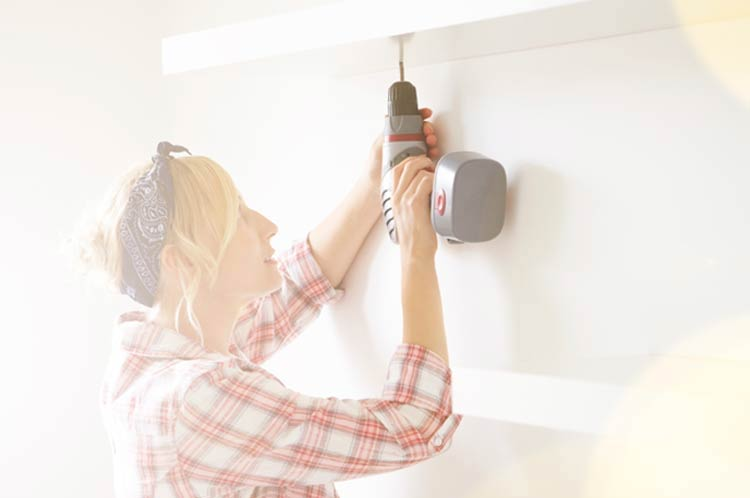 Photo of a woman using a cordless drill.