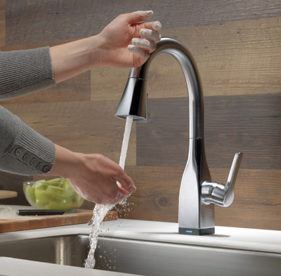 Photo of a person using a hands-free faucet.