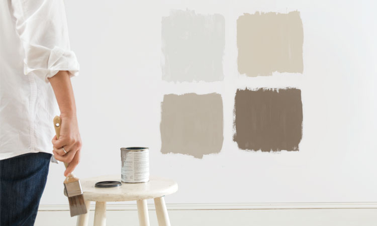 A woman standing back, assessing four test patches of paint to see which color she likes.