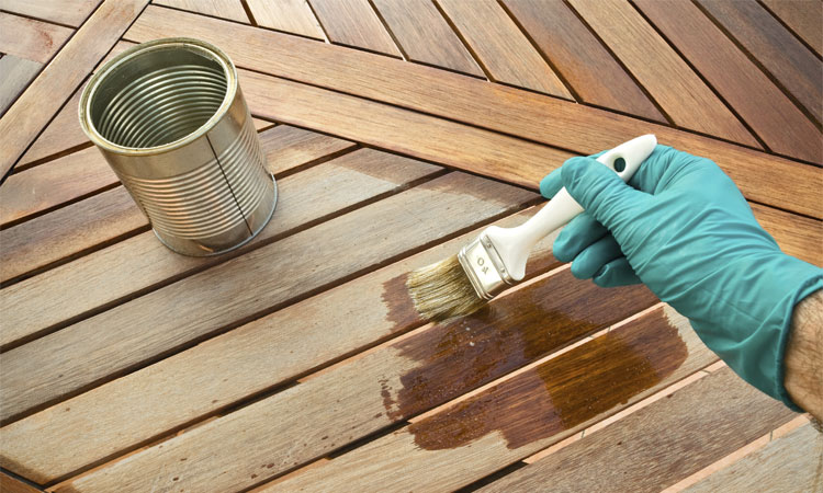 Photo of someone staining their deck with wood stain.