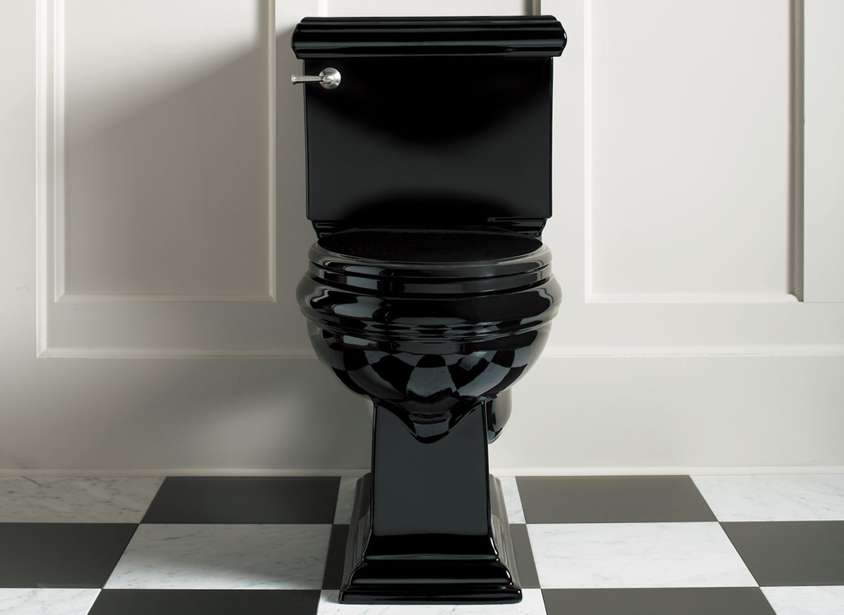 Photo of an all-black toilet in a bathroom with large black and white tiles.
