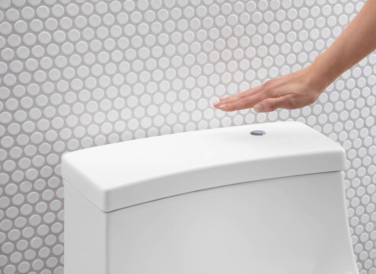 Photo of a person using a toilet's touchless technology to flush.