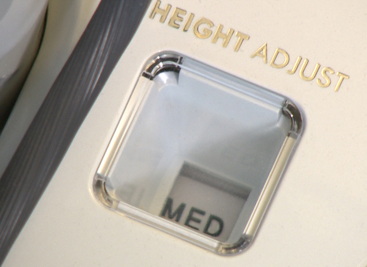 Picture of a height adjustment setting on a vacuum. Setting is at medium.