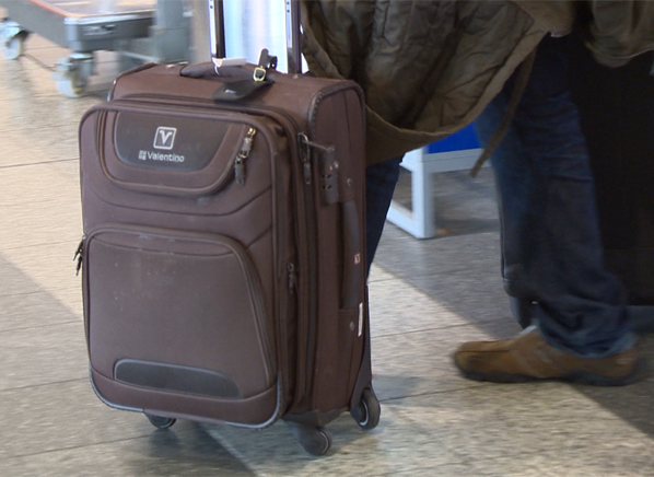 Photo of a man standing with a four-wheeled suitcase.